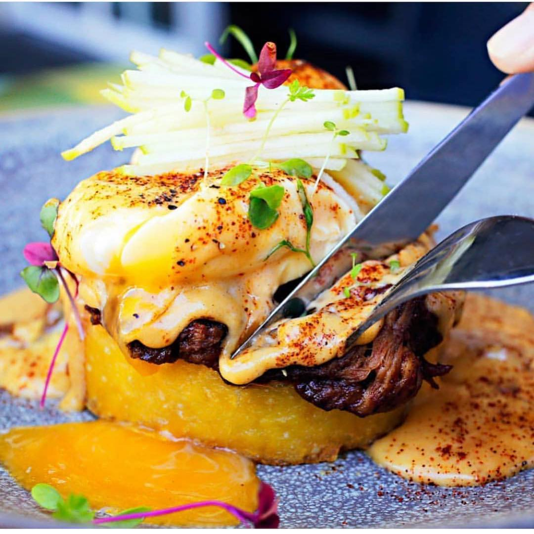 Potato Hash dish: BBQ pulled pork on a crispy hash brown with poached eggs, green apple and bbq hollandaise sauce